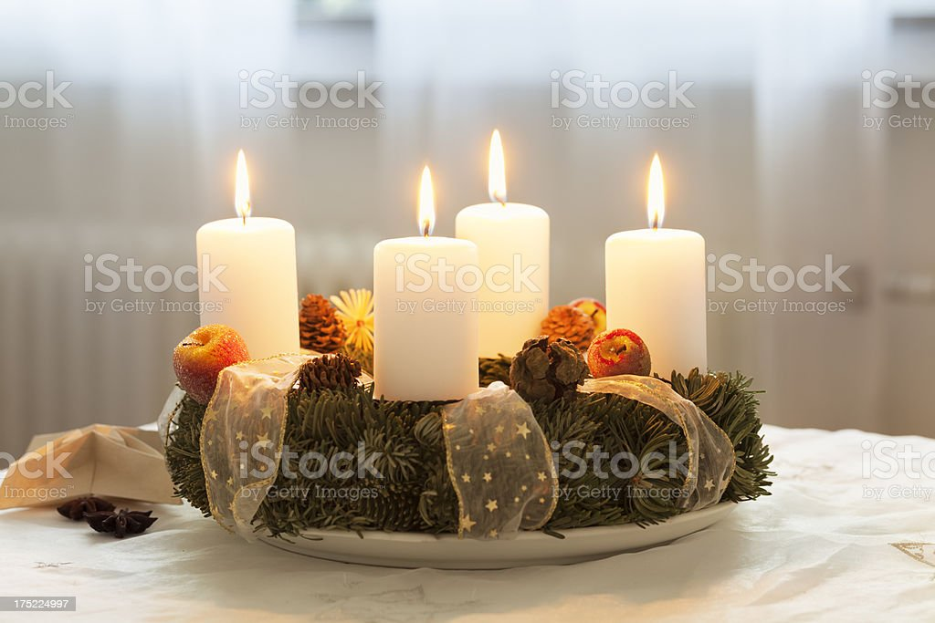 Advent wreath with 4 burning candles on table royalty-free stock photo