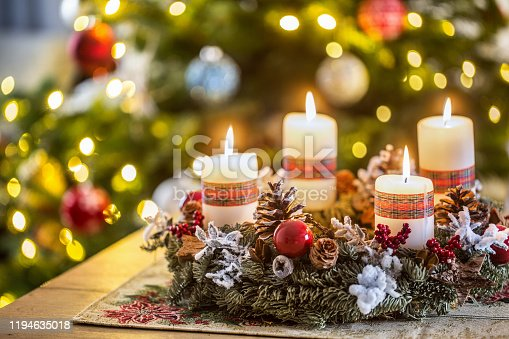 Advent wreath with four white burning candles christmas ball and decorations on a wooden background with festive atmosphere.