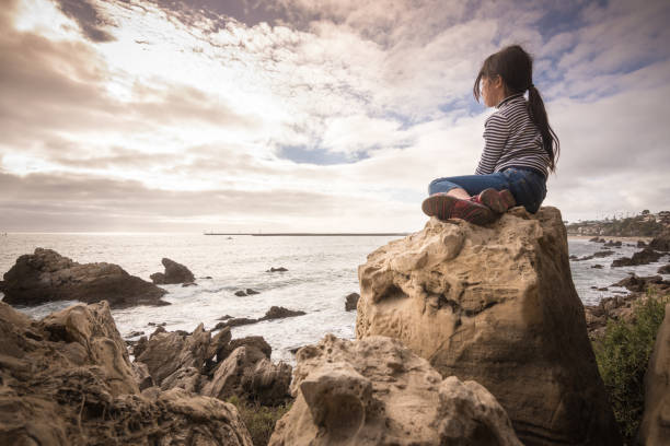 Adventerous little girl sitting on rock looking at ocean view stock photo