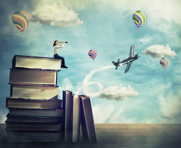 Adventure concept Surreal view as a young woman student stand on the top of a huge pile of books holding a spyglass looking far at horizon. Adventure concept, as airplane and hot air balloon fly out of the magic book. dreamlike stock pictures, royalty-free photos & images