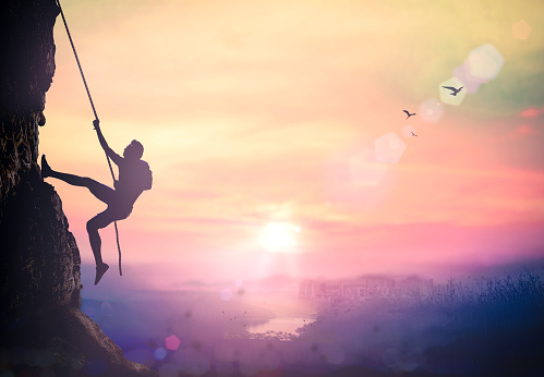Silhouette bold heroic man try to climb with rope over natural rocky wall wide valley autumn sunset mountain background