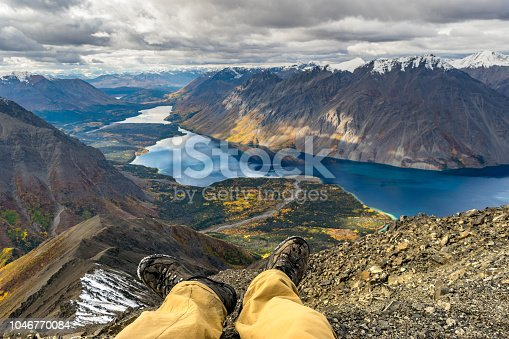 Adventure concept, resting male legs in front of the stunning landscape. Yukon, Canada