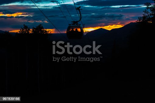 A couple goes down the gondola, silhouetted by the glow of the burning sunset behind them.