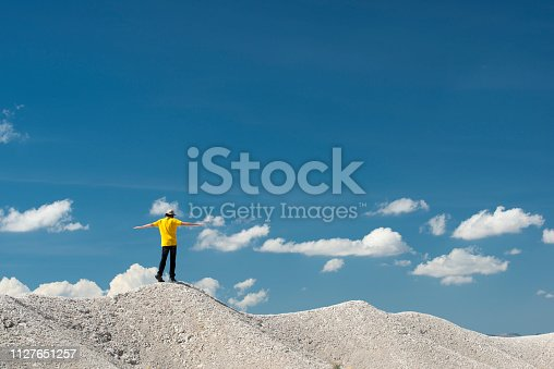 One man walking on top of a white hill, balancing with open arms. Blue sky on the background in Texas, USA.