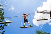 Adventure park fun boy on ropes course