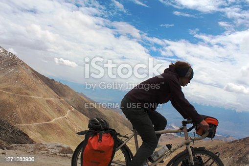 Khardungla Pass, Ladakh, Kashmir, India -August 14, 2012 : A tourist woman cycling on the road to Khardungla Pass. Cycling to Khardungla Pass is one of the most challenging yet rewarding cycling expeditions in the world.