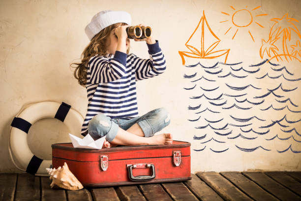 Adventure Happy kid playing with toy sailing boat indoors. Travel and adventure concept sailor stock pictures, royalty-free photos & images