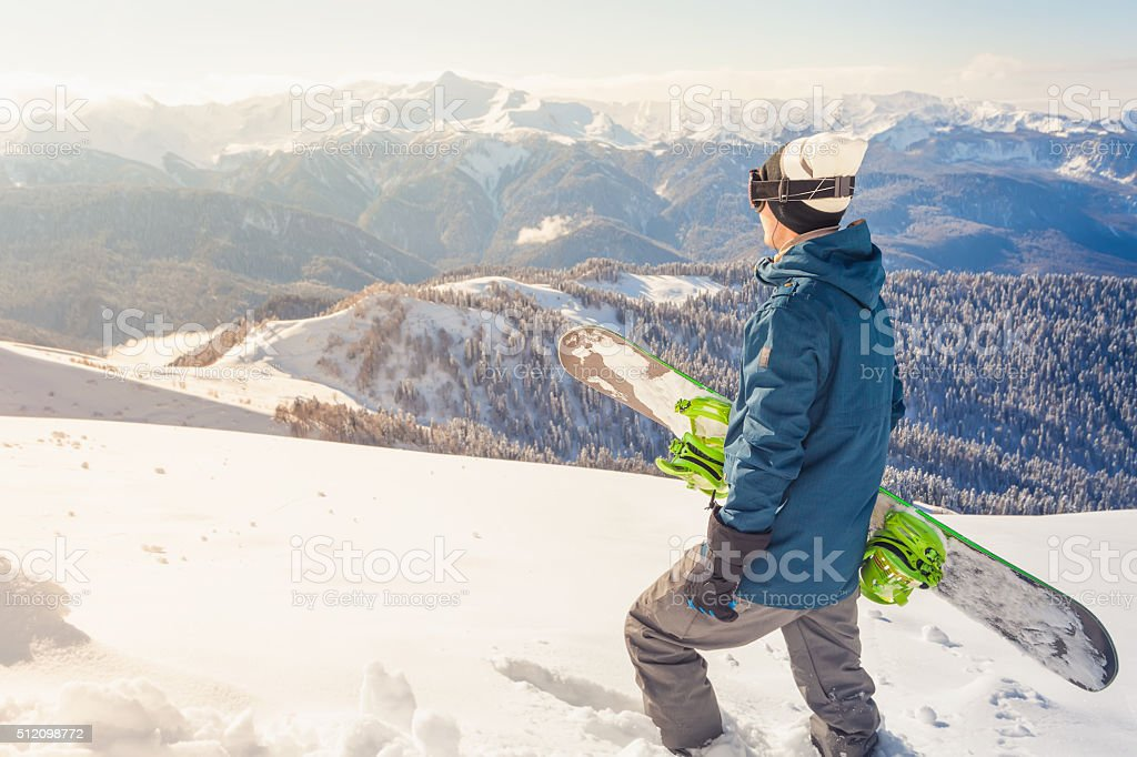 Adventure to winter sport. Snowboarder man hiking at mountain stock photo
