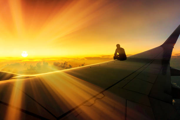 Adventure Travel Conceptual Photo of Silhouette of Man Sitting on Airplane Wing Watching Stunning Sunset World Destination stock photo
