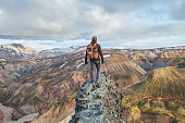 adventure travel, hiking in Iceland with backpack, tourist looking at colorful landscape of Landmannalaugar