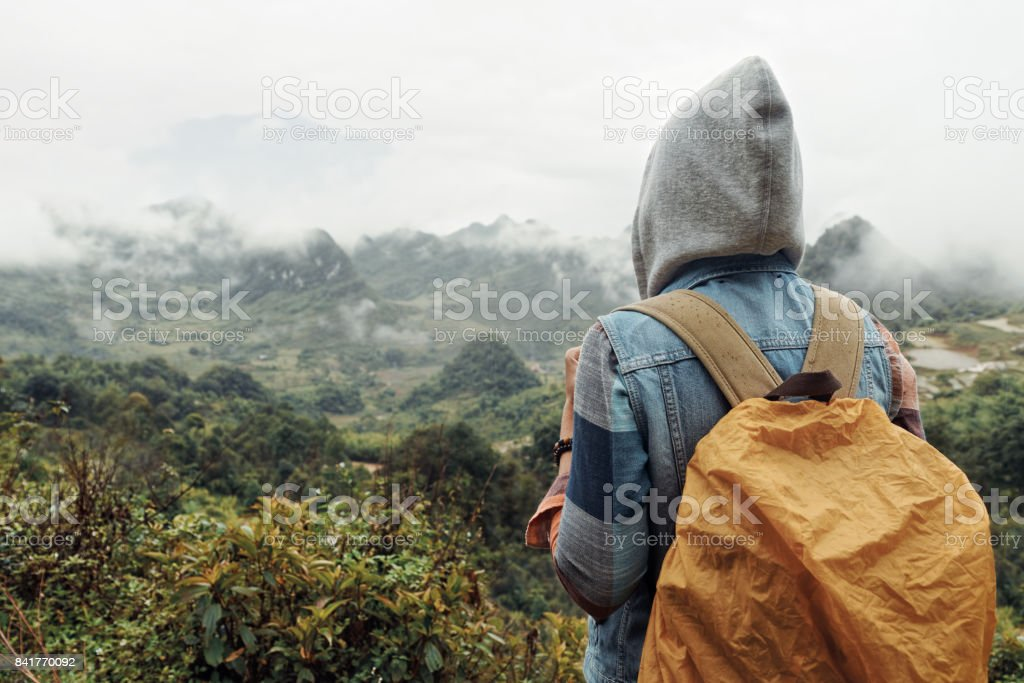 Adventure travel woman with a backpack in the mountains during a rain. stock photo