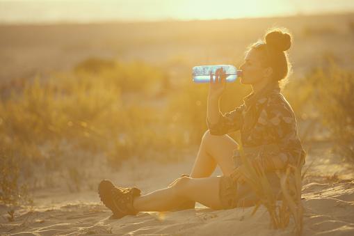 adventure traveller woman on seacoast at sunset drinking water