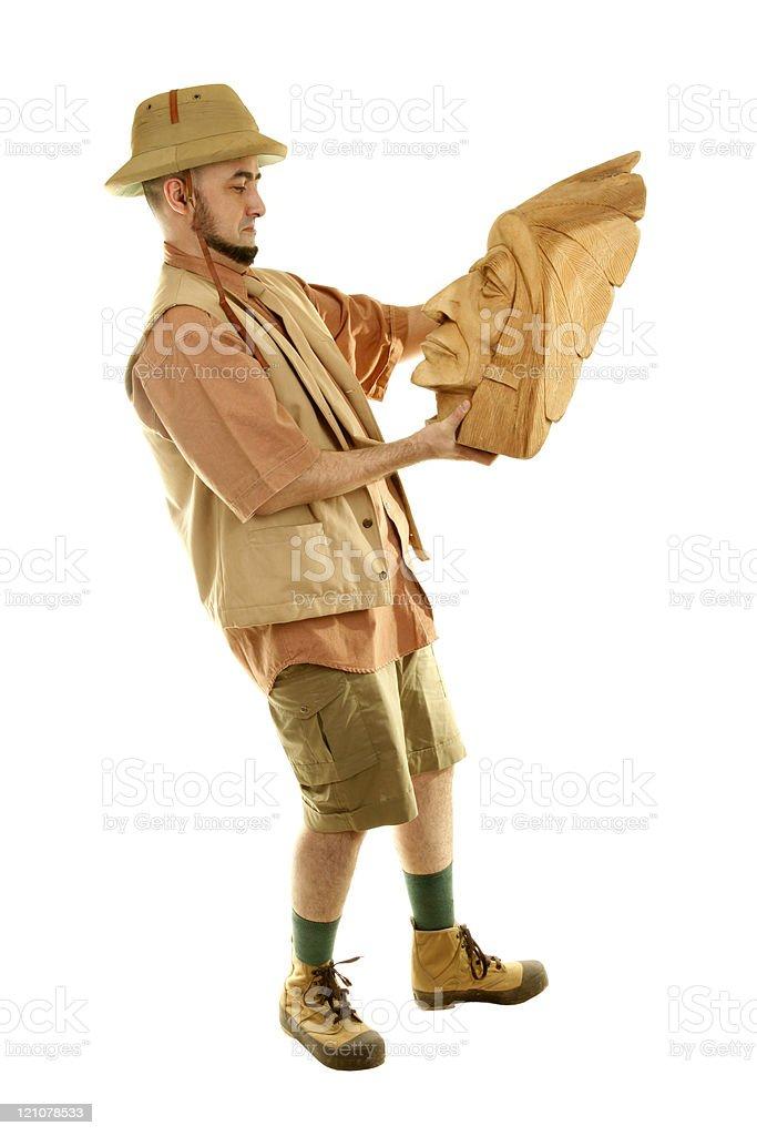 Adventurer explorer is holding wooden indian idol stock photo