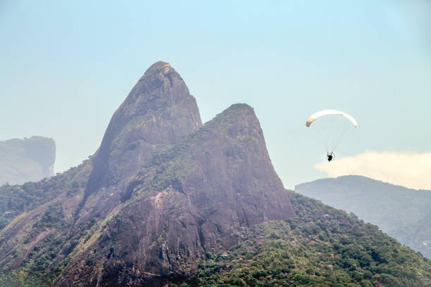 Adventurer flies with paraglider in Ipanema, Rio de Janeiro, with the Dois Dois Hermanos in the background. stock photo
