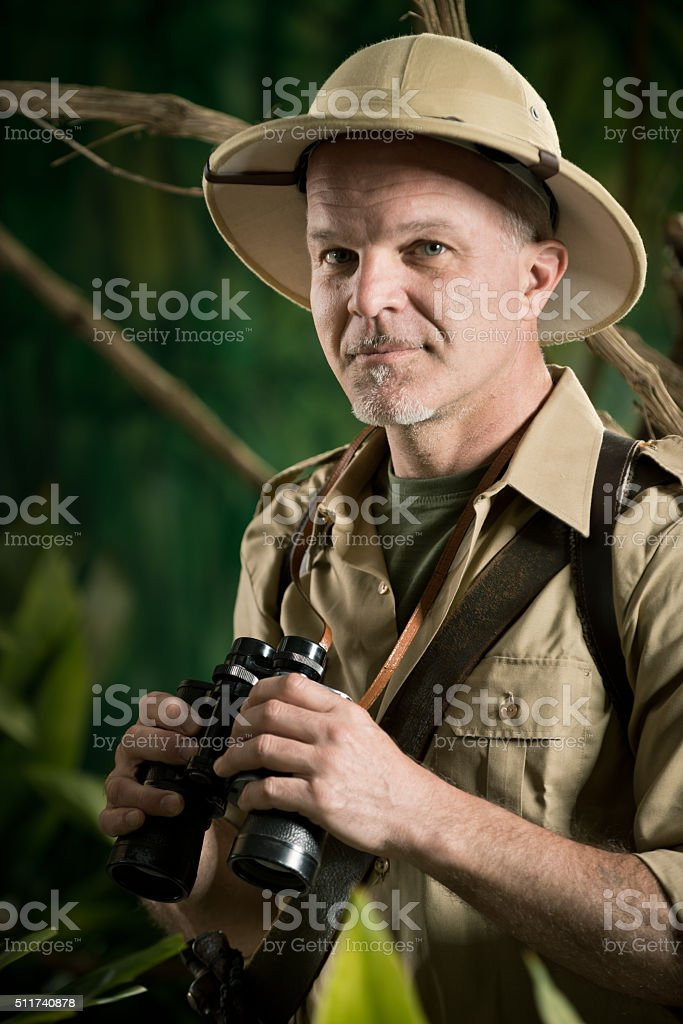 Adventurer in the jungle with binoculars stock photo