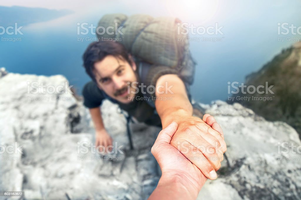 adventurers helping each other to climb the mountain stock photo