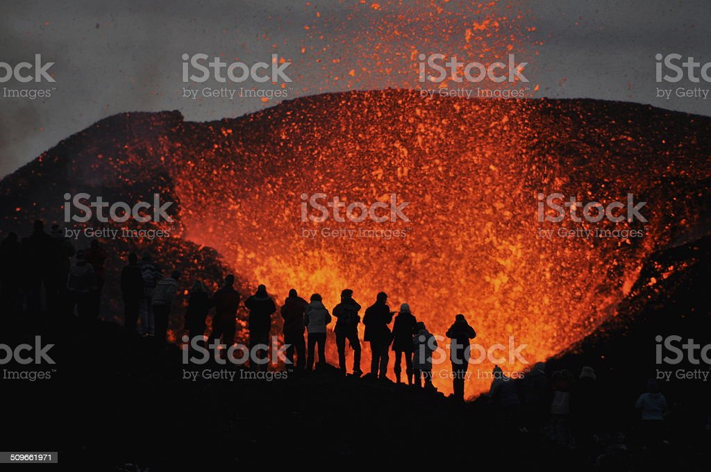 Adventurers witnessing a Volcanic Eruption stock photo