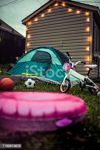 Illuminated shed in the backyard at night. There is a small garden, a camping tent installed, sport balls, a bike and a pink inflatable ring.