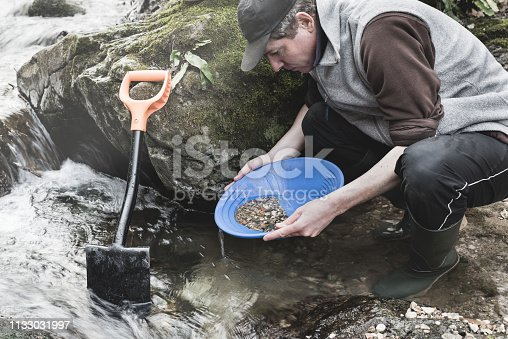 Man with blue pan for gold or batea, rubber boots and shovel, is looking for gold in a creek. Gold panning. Moody instagram look