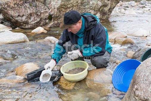 Gold digger who washes the sand in the sluice box and modern manual equipment for searching of gold (batea or gold pan, sluice box, plastic bucket) at a mountain creek