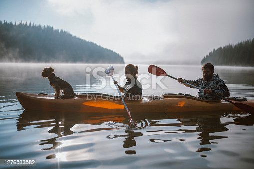 Couple is kayaking with their dog