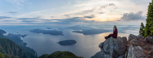 Adventurous Hiker on top of a Mountain during Sunset