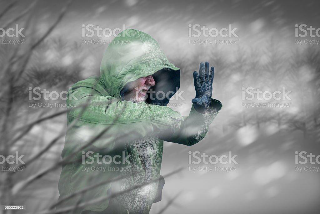 Adventurous man caught in snowstorm or winter blizzard. stock photo