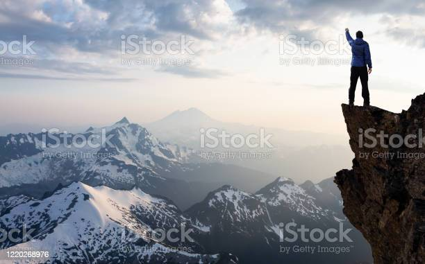 Photo of Adventurous Man Hiker With Hands Up on top of a Steep Rocky Cliff
