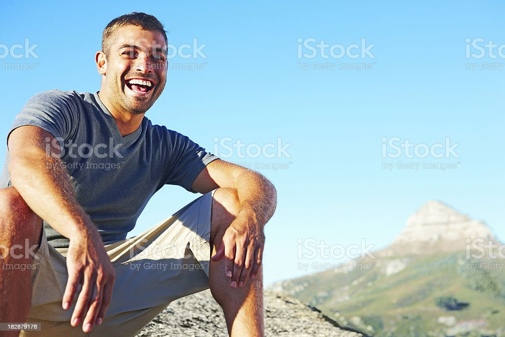 Adventurous man sitting on rock against natural background stock photo