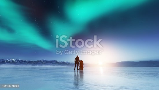 istock Adventurous man standing with a backpack, looking at aurora. 951027630