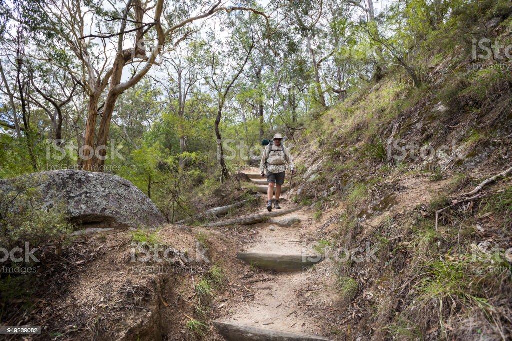 Adventurous retiree hiking on a rough dirt track stock photo