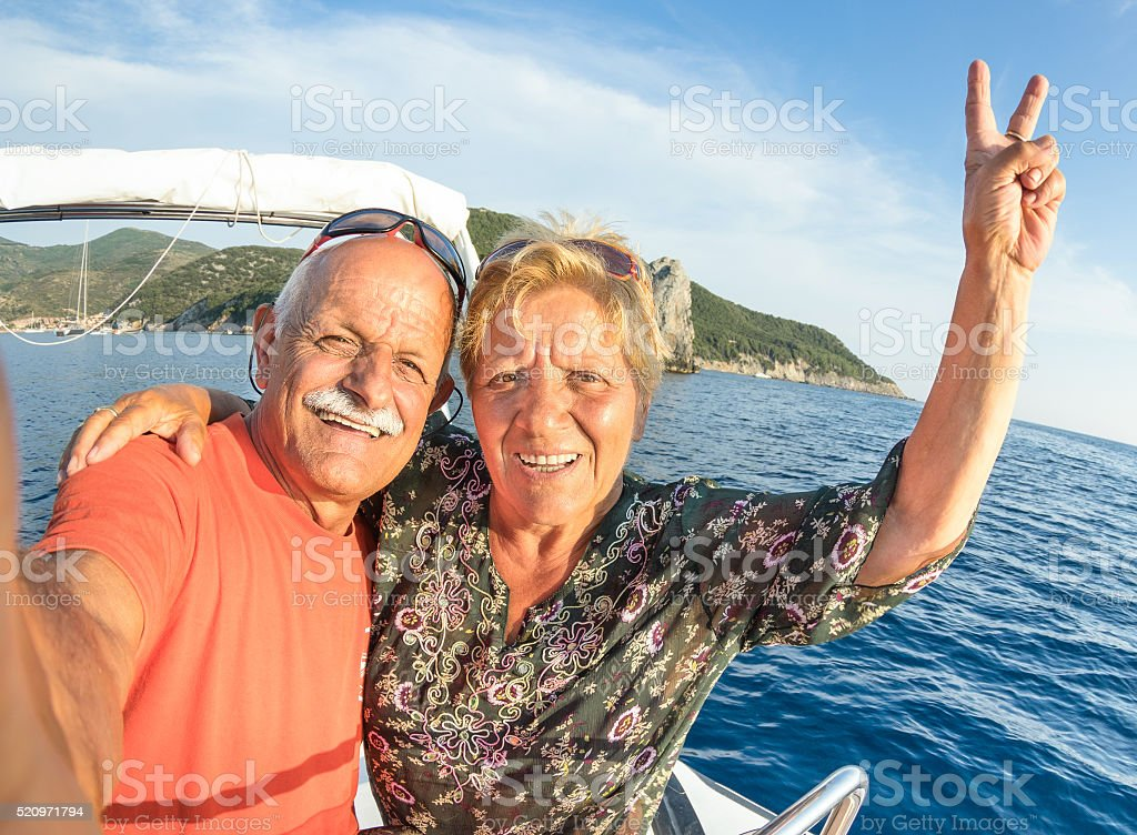 Adventurous senior couple taking travel selfie at Giglio Island圖像檔