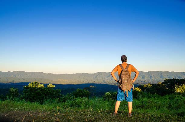 Adventurous traveler viewing top rocky mountain & valley stock photo