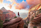 Adventurous Woman at the edge of a cliff is looking at a beautiful landscape view in the Canyon during a vibrant sunset. Taken in Zion National Park, Utah, United States. Sky Composite.