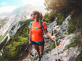 Young woman with sunglasses, wearing an orange shirt and a blue backpack, hiking in the mountains on a summer day. Adventurous woman hiking in the Alps alone. Scenic views on the mountains.