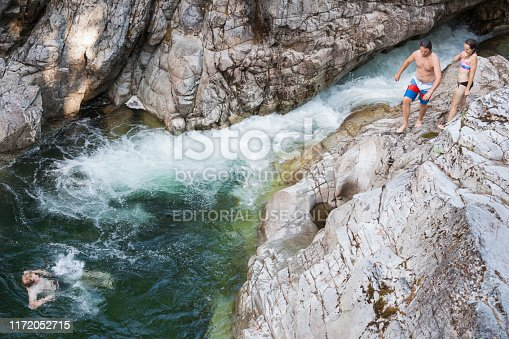 Vancouver Island, Canada - July 14, 2015: Caucasian man and woman in 20's climb rocks and jump into the water at Little Qualicum Falls near  Campbell River