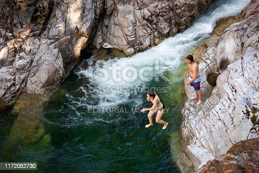 Vancouver Island, Canada - July 14, 2015: Caucasian woman jumps into the water while a young man watches from a  rock at Little Qualicum Falls near  Campbell River