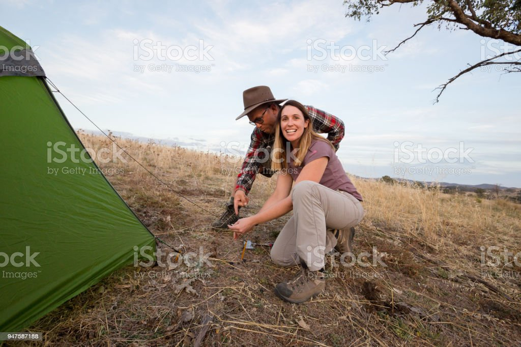 Adventurous young couple help each other set up a tent in beautiful afternoon light stock photo