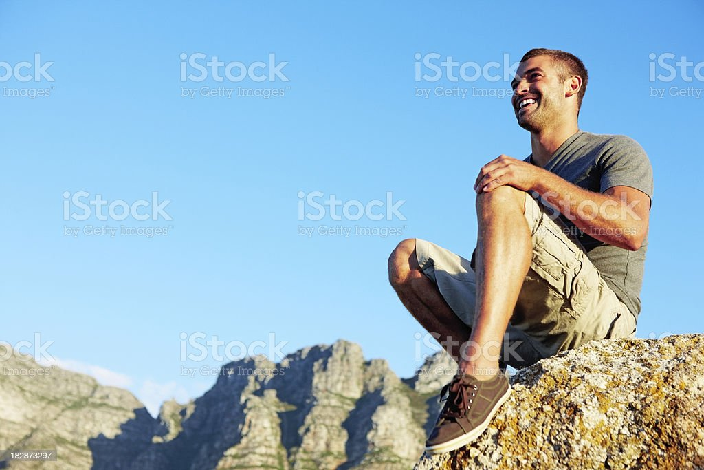 Adventurous young guy sitting on rock against blue sky royalty-free stock photo
