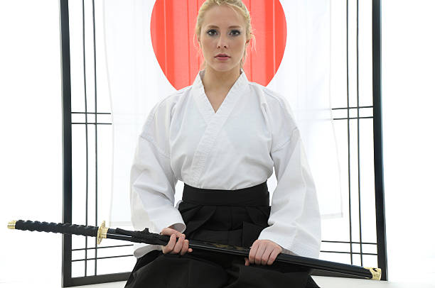 Adversarial beauty Martial artist with sword in her dojo.    adversarial stock pictures, royalty-free photos & images
