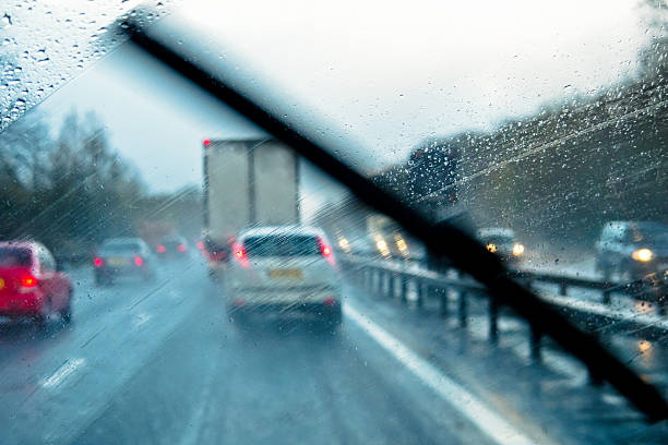 Adverse Driving Conditions Rain through the window of a car on a motorway windshield wiper stock pictures, royalty-free photos & images