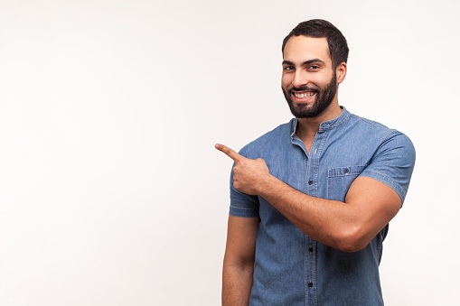 Advertise here! Positive bearded man pointing finger away paying your attention at empty space for advertisement, looking at camera with toothy smile. Indoor studio shot isolated on white background