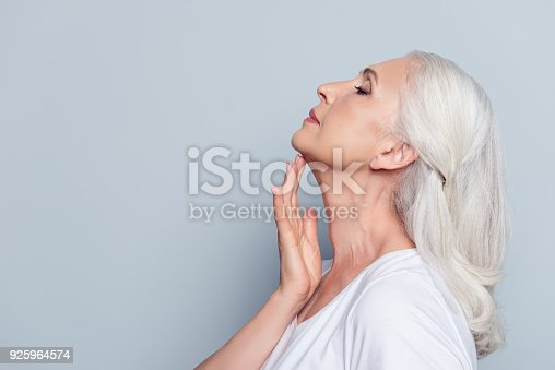istock Advertisement concept. Close up profile with copy space of nice, charming, aged woman, touching her skin of neck with hand over grey background 925964574