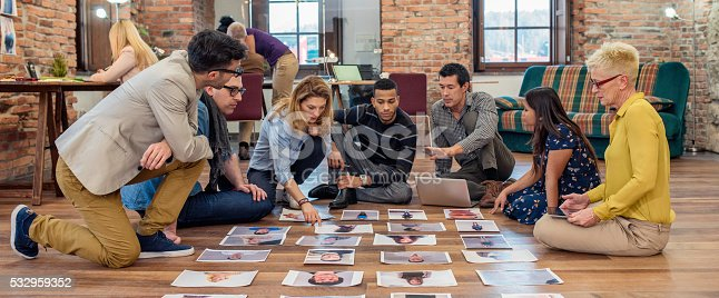Panoramic shot of advertising agency team choosing model for campaign among pictures spread out on wooden floor.