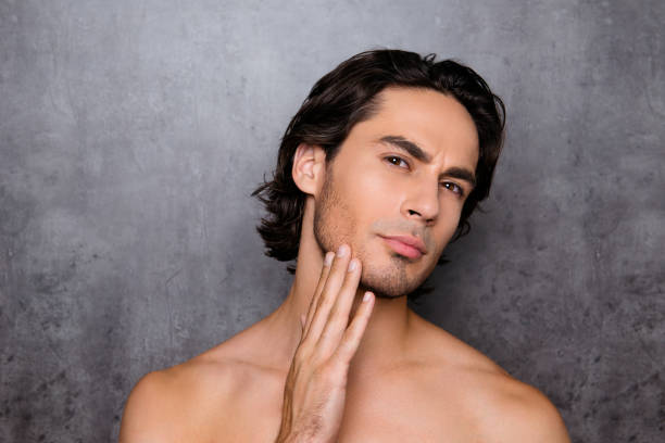 Advertising and barber shop, beard cut and styling concept. Close up portrait of nude hot guy, touching his bristle, chin, has perfect skin and hair, isolated on grey background stock photo