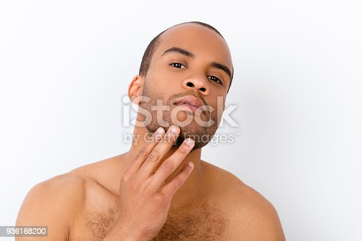 Advertising and barber shop, beard cut and styling concept. Close up portrait of nude african guy, touching his bristle, isolated on white background