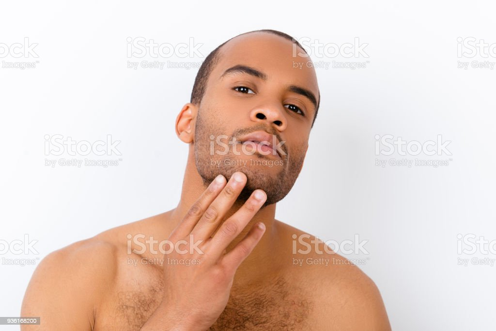 Advertising and barber shop, beard cut and styling concept. Close up portrait of nude african guy, touching his bristle, isolated on white background stock photo