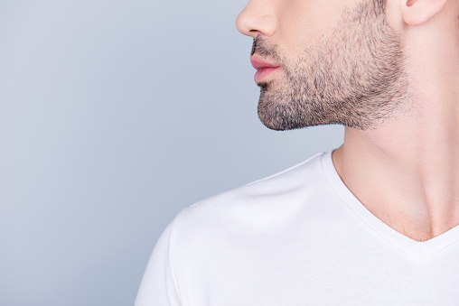 istock Advertising barbershop concept. Profile close up half face cropped portrait of handsome brunet  man with perfect stunning cut of his beard, in white t-shirt isolated on light grey background 982342474