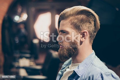 698023272 istock photo Advertising barbershop concept. Profile side portrait of confident handsome red bearded young man. He has a perfect stunning hairstyle, modern haircut 939974882