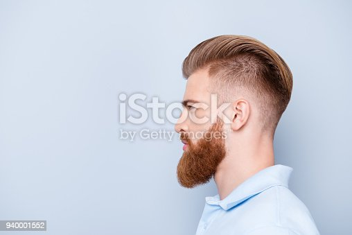 698023272 istock photo Advertising barbershop concept. Profile side portrait of confident handsome red bearded young man. He has a perfect stunning hairstyle, modern haircut 940001552